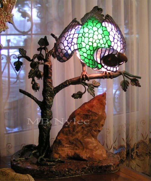 Lampa witrażowa ww14. Papuga wykonana jest z witrażu, drzewo ze stali, podstawa z kamienia. Lampa do oglądnięcia w siedzibie firmy.